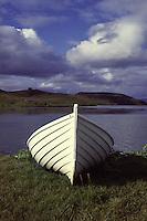ISLANDA, paesaggio naturale. Una piccola barca di legno bianco è ormeggiata sulla riva di un fiordo.
