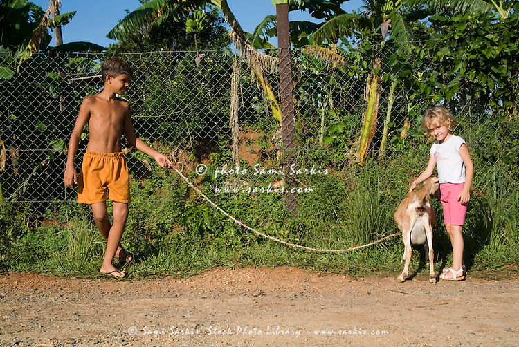 Girl patting a goat while the goat's owner watches in Vinales, Cuba.