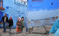 People walking in a street, painted blue, in the medina or old town of Chefchaouen in the Rif mountains of North West Morocco. Chefchaouen was founded in 1471 by Moulay Ali Ben Moussa Ben Rashid El Alami to house the muslims expelled from Andalusia. It is famous for its blue painted houses, originated by the Jewish community, and is listed by UNESCO under the Intangible Cultural Heritage of Humanity. Picture by Manuel Cohen