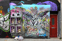 Winged devils and angels spray paint graffiti, incorporating electricity meters on a wall with doorway and two garbage bags of a street in Brick Lane area, London, UK. Picture by Manuel Cohen