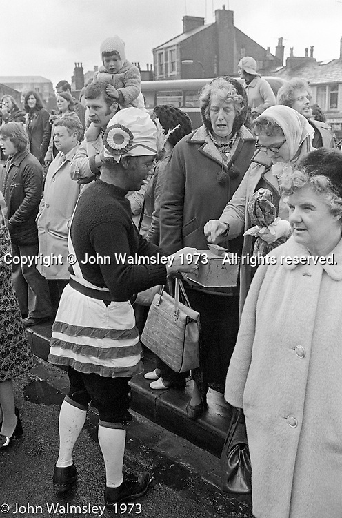 """The """"Nutters' Dance"""", Bacup, Lancashire  1973.  On Easter Saturday every year the """"Coco-nut"""" dancers gather at one boundary of the town and dance their way across to the other accompanied by members of the Stackstead Silver Band, collecting for charity as they go.  It includes a short stop in one of the pubs."""