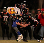 HOWARD, SD - NOVEMBER 8:  Jordan Genzlinger #11 and Luke Loudenburg #23 from Howard bring down Christopher Klemme #25 from Alcester Hudson in the first half of their Class 9A Semifinal game Saturday night in Howard. (Photo by Dave Eggen/Inertia)