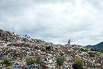 Burmese boy walks thought the rubbish dump site on the way home from school in the outskirts of the border town of Mae Sot, Thailand August 16 2017.