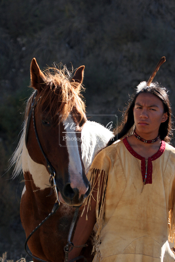 A Native American Indian boy wearing a feather standing next to a horse