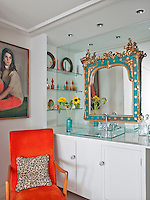 A bright orange velvet armchair and an ornate green and gold hand-painted mirror add bursts of colour to the otherwise all white en-suite bathroom
