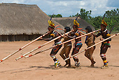 Xingu Indigenous Park, Mato Grosso State, Brazil. Aldeia Afukuri (Kuikuro). Festival of Taquara; warriors and girls dancing and playing Taquara bamboo flutes.