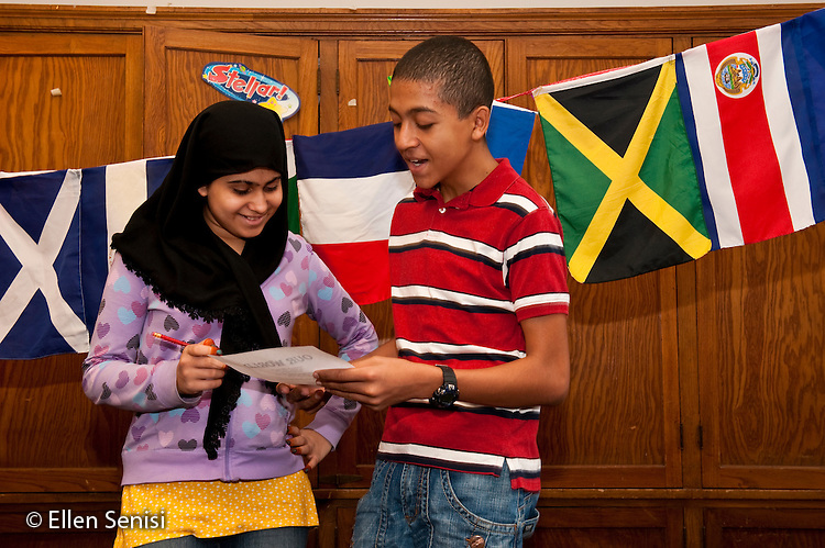 MR / Schenectady, NY. Mont Pleasant Middle School (urban public school). English as a Second Language classroom (ESL). Student (girl at left; 14; grade 8; Afghani-American) listens to student (boy at right; 13; grade 8; recent immigrant) read his classroom writing assignment. MR: Taj1, Sod1. ID: AJ-esl1. © Ellen B. Senisi