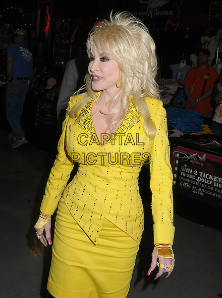 Dolly Parton signs autographs for a limited number of lucky fan winners during the 2011 CMA Music Festival at Fan Fair Exhibit Hall at the Nashvile Convention Center, marking her first autograph session at the event since the mid-'70s. Nashville, Tennessee, USA 11th June 2011.half length yellow dress gold profile skirt jacket beads beaded.CAP/ADM/LF.©Laura Farr/AdMedia/Capital Pictures.