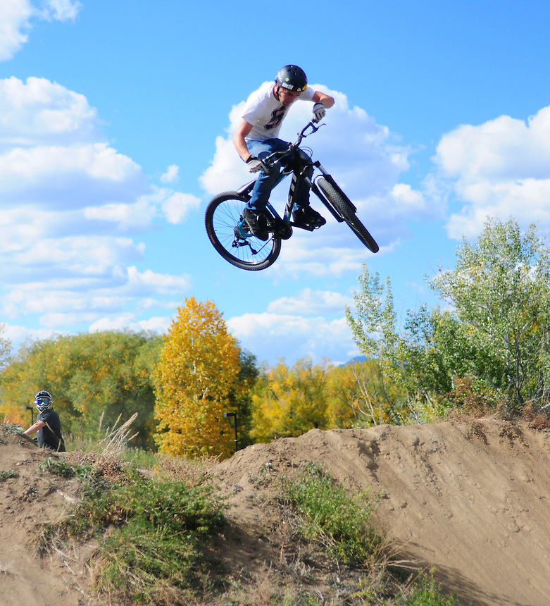 """A mountain biker bmx dirt jumping at the """"Sunset trails"""" in Lakewood, Colorado on October 19, 2008. alternative sports, extreme, danger, foliage, clouds, air, dirt, sunset trails"""