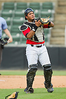 Kannapolis Intimidators catcher Angel Rosario (10) tosses his mask as he settles under a foul pop fly during the South Atlantic League game against the Greensboro Grasshoppers at CMC-Northeast Stadium on July 13, 2013 in Kannapolis, North Carolina.  The Intimidators defeated the Grasshoppers 7-5.   (Brian Westerholt/Four Seam Images)