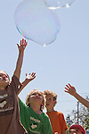 Port Townsend Farmers Market, kids chasing giant bubbles, Washington State, Pacific Northwest, USA,