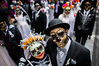 Young couples, costumed as La Catrina, a Mexican pop culture icon representing the Death, walk through the town during the Day of the Dead celebrations in Mexico City, Mexico, 29 October 2016. Day of the Dead (Día de Muertos), a syncretic religious holiday combining the death veneration rituals of the ancient Aztec culture with the Catholic practice, is celebrated throughout all Mexico. Based on the belief that the souls of the departed may come back to this world on that day, people gather at the gravesites in cemeteries praying, drinking and playing music, to joyfully remember friends or family members who have died and to support their souls on the spiritual journey.