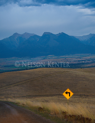 a road sign reflects light on a cloudy evening in western montana