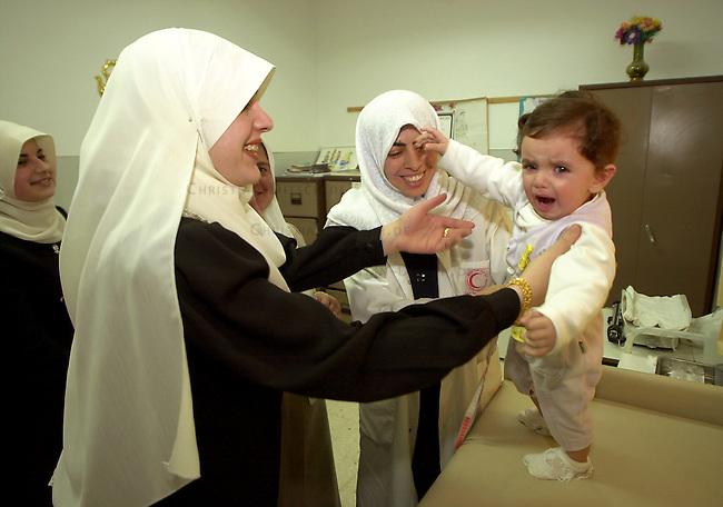 Medizinische Hilfe fuer Palaestinenser<br /> Seit Oktober 2000 ist die palaestinensische Stadt Bedia nahe Nablus nicht mehr von Israel per Auto zu erreichen. Von der israelischen Regierung aufgeschuettete Strassensperren sind fuer Fahrzeuge jeglicher Art unueberwindbar geworden. In der 10.000 Einwohnerstadt mangelt es an nahezu allem. Medizinische Versorgung gab es letztmals im Maerz diesen Jahres.<br /> Die rund 500 Mitglieder zaehlende israelisch-palaestinensische Menschenrechtsorganisation Physicians for Human Rights (PHR) hat nach einem Hilferuf des palaestinensischen Roten Kreuzes im Rathaus von Bedia eine medizinische Versorgung der Bevoelkerung durchgefuehrt (Medical Day). Rund 600 Personen konnten von 11 Aerzten und etlichen Krankenschwestern nach bis zu acht Stunden Wartezeit behandelt werden. Die Mediziner mussten an diesem Tag die dreifache Menge an Menschen versorgen. Die Patienten kamen zum Teil aus bis zu 35 km Entfernung. Das Gesundheitssytem in den palaestinensichen Autonomiegebieten ist nach Angaben der PHR seit dem Beginn der &quot;Operation Schutzschild&quot; kollabiert. Die meisten der erkrankten Kinder leiden an Atemwegs- und Viruserkrankungen.<br /> Die PHR existieren seit der ersten Intifada 1988 und haben sich zum Ziel gesetzt, in den palaestinensischen Gebieten ohne Ansehen der Herkunft und Zugehoerigkeit medizinische Hilfe zu leisten. Fuer schwer und chronisch Erkrankte versuchen die PHR-Mitarbeiter Transporte und klinische Versorgung in israelische und us-amerikanische Hospitaeler zu ermoeglichen. Bis auf zwoelf Hauptamtliche arbeiten alle anderen Mitglieder ehrenamtlich. Die Organisation finanziert sich durch Geld- und Sachspenden. Eine Zusammenarbeit mit israelischen Gesundheitsinstitutionen wird von Regierungsseite abgelehnt.<br /> Hier: Eine Mutter mit ihrem fieberkranken Kind bei der Versorgung durch eine Krankenschwester.<br /> Bedia / Israel, 18.05.2002<br /> Copyright: Christian-Ditsch.de<br /> [Inhaltsveraendernde Manipulation des