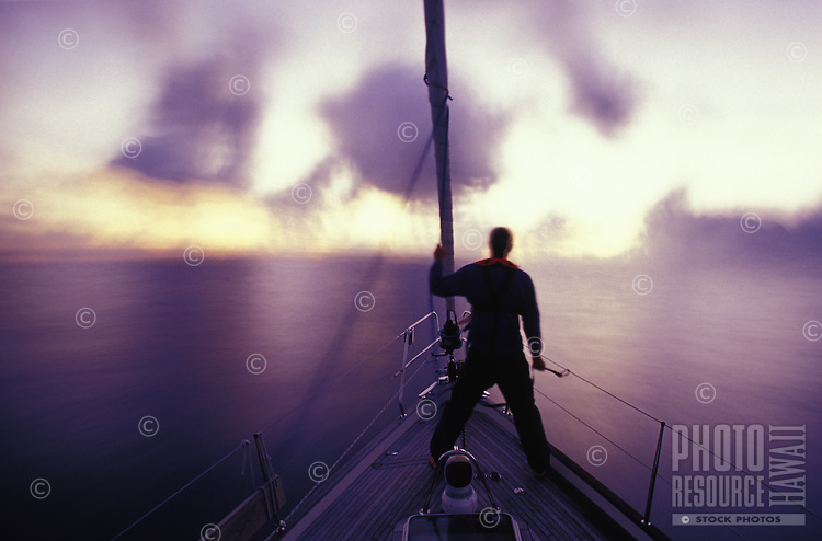 Man standing on bow of sailboat in open ocean looking out over surreal after-sunset sea
