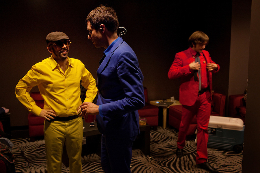 "Los Angeles, California, November 27, 2010 - Three-quarters of the band Ok Go, from left, bass guitarist/singer, Tim Nordwind (yellow), lead singer/guitarist, Damian Kulash (blue), and Andy Ross (red), drummer, prepare in their dressing room before their show at the Nokia Club. OK Go was wrapping up a 16-month world tour by playing a song for Yo Gabba Gabba! during the day and later a final show at the Nokia Club. The Grammy Award-winning band has earned considerable fame for their creative, often low-budget music videos that are released on YouTube. Many have gone viral, including the 2006 video for ""Here It Goes Again"", where the band performs a complex routine on treadmills. It has received over 50 million views to date. Kulash says the band left their major label and began their own to assert more creative control over their music and their videos. Adding, ""We're among the first musicians to view our YouTube videos as standalone artistic output, not advertisement for our recordings, and it shows in the numbers: over the past decade, we've sold a little over 600,000 records globally, and our videos have combined views in excess of 125 million.""."