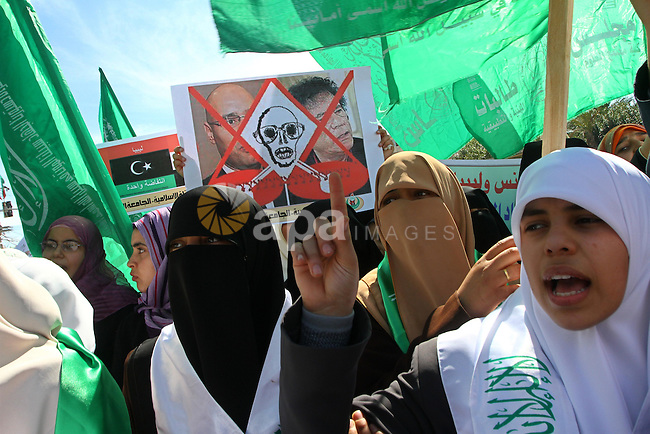"Palestinian students hold up placards during a protest against Libyan leader Moamer Kadhafi, in Gaza City on February 22, 2011. Gaza's Hamas rulers heaped condemnation on ""the massacres"" of anti-government protestors in Libya committed by regime of embattled veteran leader Moamer Kadhafi. Photo by Ashraf Amra"