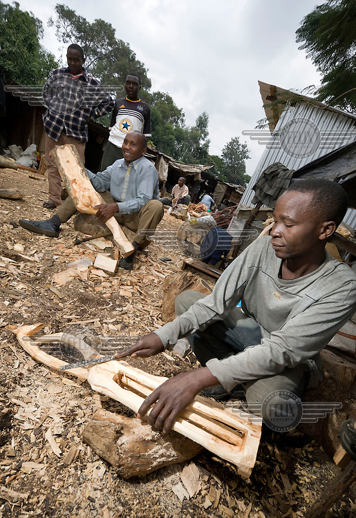 Wood carvers at work in Nairobi, behind him special, tropical hardwood illegally cut from Ngong forest. Ngong forest is a fenced and  protected sanctuary. It is a nature reserve that has an abundance of animals and wildlife and acts as a physical division between the rich and poor areas of Nairobi. Illegal deforestation is a serious problem as the forest is full of rare, hardwood species that are sold to souvenir carvers in Nairobi who make wooden animals in all sizes for tourists in Kenya.