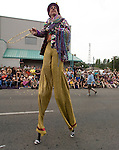 Stilt walker Bob Watson throws beads to the crowd in the 21st annual Summer Solstice Parade held Saturday, June 20, 2009 in Seattle, Wa. The parade was held Saturday, bringing out painted and naked bicyclists, bands, belly dancers and floats. (Jim Bryant Photo © 2009)