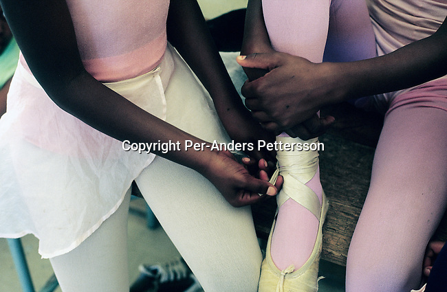 Ballet students dress before a yearly performance on November 25, 2000 in Guguletu, a big township outside Cape Town, South Africa. About 200 children dance ballet in a school called Dance For All, which teaches unprivileged children dance after school. Many children are talented and the discipline taught during the dance classes has helped many to improve their concentration in school. The township is struggling with high unemployment, crime and high levels of HIV/Aids. (Photo by: Per-Anders Pettersson) .....