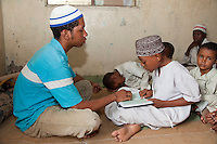 Zanzibar, Tanzania.  Imam Helping Young Boy in a Madrassa (Koranic School) Read Verses in the Koran.