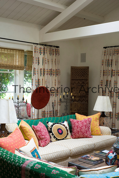 A rare mid-20th century Nigerian wooden door stands in the corner of the sitting room behind a sofa covered with multi-coloured and patterned cushions