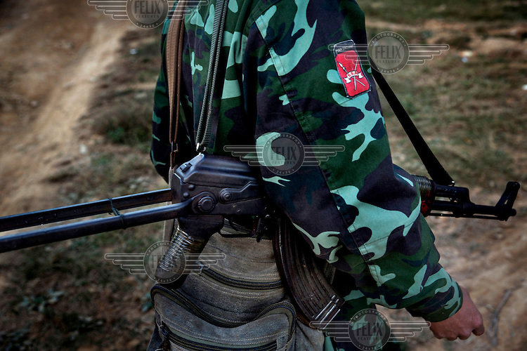 A Shan State Army - South rebel soldier walks through Bang Laem Village in a Shan State Army - South controlled area of Shan State.
