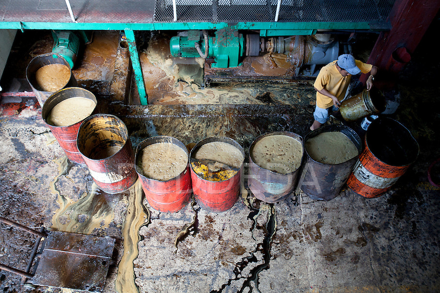 A man fills barrels of molasses, a byproduct of manufacturing raw sugar from sugar cane, sit and leak inside the URSUMCO (Universal Robina Sugar Milling Corporation) cane sugar mill near Bias City on Negros Island, Philippines.