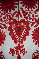 Rough linen is embroidered with a red heart-shaped pattern and flowers