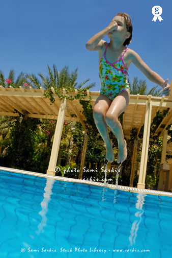 Girl (6-7) jumping into swimming pool, holding nose (Licence this image exclusively with Getty: http://www.gettyimages.com/detail/sb10065474ce-001 )