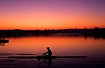 Silhouetted Crewman rowing creating wake, sunrise, looking west  Seattle, Washington USA