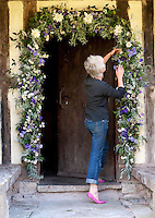 Portrait of artist and flower arranger Caroline Ede decorating the entrance to her cottage with flowers