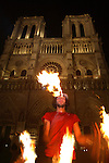 The night view of a street performer juggling flames in front of Notre-Dame Cathedral. Paris. France