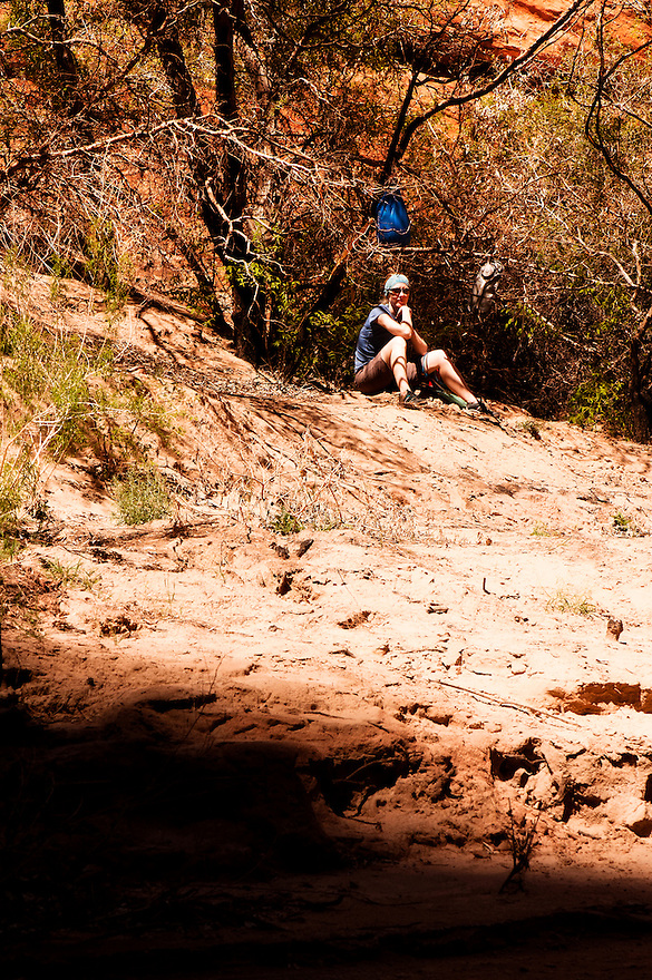 A hiker takes a break in the shade along the Paria River in northern Arizona.