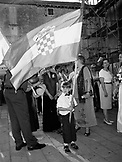 CROATIA, Dalmatian Coast, portrait of a boy holding flag with people in the background B&W