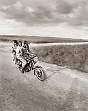 DOMINICAN REPUBLIC, three friends enjoying a motorcycle ride on a rural road near Casa de Campo (B&W)