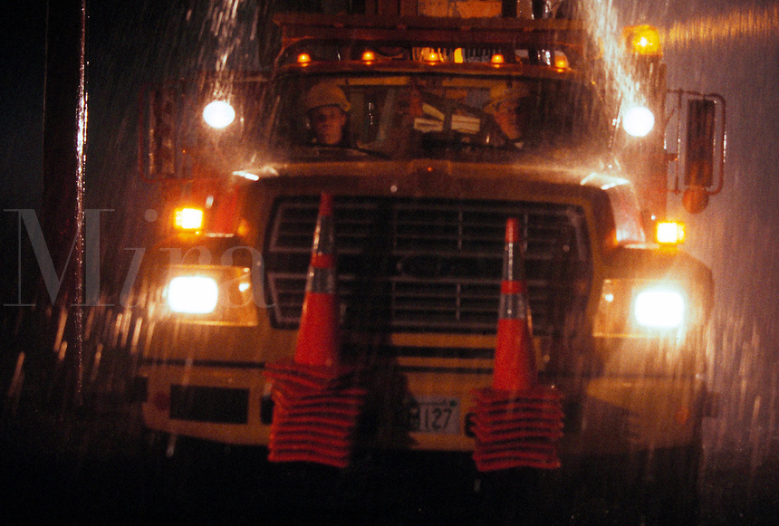 Electric line workers in truck during heavy rainstorm.