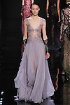 """Model walks runway in a lilac re-embroidered lace dress with silk chiffon cascade skirt from the Reem Acra Fall 2016 """"The Secret World of The Femme Fatale"""" collection, at NYFW: The Shows Fall 2016, during New York Fashion Week Fall 2016."""