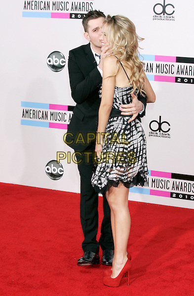 MICHAEL BUBLE & LUISANA LORELEY.Arrivals  to the 2010 American Music Awards held at Nokia Theatre L.A. Live in Los Angeles, California, USA..November 21st, 2010.AMA AMAS AMA'S full length couple fiance print dress suit grey gray red profile shoes blue tie white shirt black side profile arm around waist kiss kissing .CAP/PE.©Peter Eden/Capital Pictures.