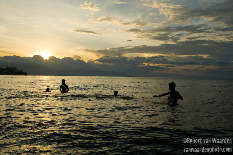 Silhouetted fishermen bring in their net by hand at Anturan, Northern Bali, Indonesia.