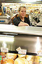 Deli worker smiling over the counter in the meat department