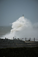 Pictured: Waves crash against the lighthouse at the seaside town of Aberystwyth, Wales, UK. Saturday 21 October 2017<br /> Re: Coastal parts of the UK is facing winds of up to 70mph as Storm Brian causes roads to close and public transport to be cancelled.<br /> Roads in Aberystwyth's seafront and at nearby Aberaeron, Wales are shut on Saturday morning as a yellow &quot;be aware&quot; Met Office warning is in place.<br /> Seven flood warnings have been issued for the west Wales coast.