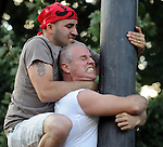 Joe Artioli of Suffield, left,  climbs over the back of Tom Puleri, of Columbus Ohio who grew up in Enfield and won this event 25 years ago, during the greased pole competition, during the last day of Our Lady of Mount Carmel Society 85th Annual Festival, Sunday, August 1 ,2010, in Enfield.