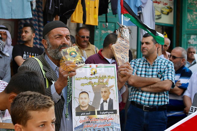 Palestinians take part in a protest in solidarity with prisoners on hunger striker in Israeli jails, in the West Bank city of Hebron, on August 23, 2019. Eight Palestinian prisoners are now on hunger strike against their administrative detention. The first to start the strike was Huthaifa Halabiya 49 days ago and other detainees followed him. Photo by Mosab Shawer