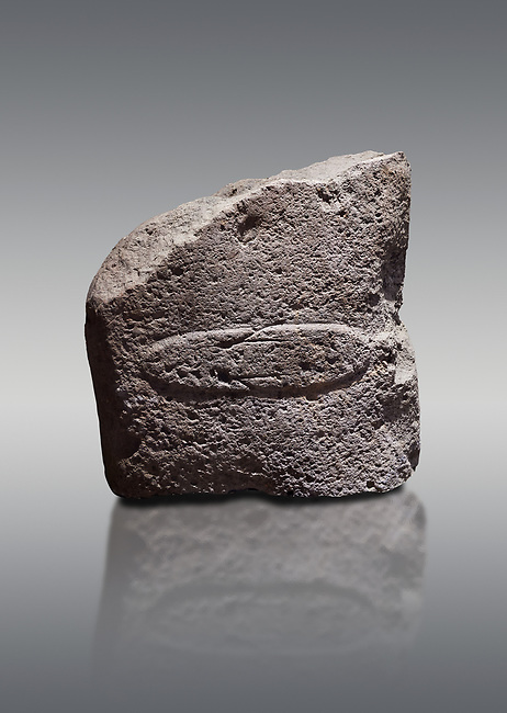 Fragment of a Late European Neolithic prehistoric Menhir standing stone with acarving of a horizontal knife on its face side.   Excavated from Montes I, Laconi. Menhir Museum, Museo della Statuaria Prehistorica in Sardegna, Museum of Prehoistoric Sardinian Statues, Palazzo Aymerich, Laconi, Sardinia, Italy. Grey background.