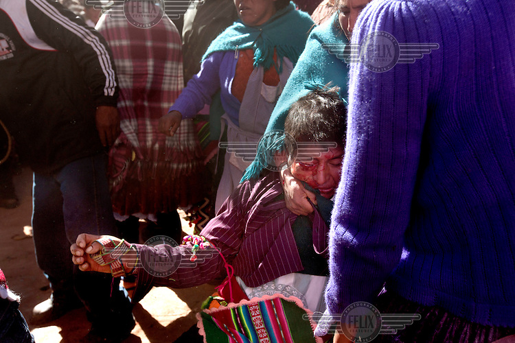 A woman pulls her injured man away during the ritual fighting in the plaza of Macha. <br /> <br /> The people of Macha and surrounding communities carry on the pre-Columbian tradition of ritual fighting. The communities gather on the plaza of Macha to fight and dance in competition with each other. The blood that is spilled is an offering to Mother Earth. In return, the people ask for rain and a good harvest. This ritual is called tinku or fiesta de la cruz since the cross is also engaged in the festivities. The cross is dressed up, given offerings and brought from communities around Macha to the church in town. This syncretic festival melds pagan, pre-christian rituals with Catholic practice. /Felix Features