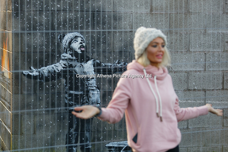 """Pictured: People arrive to see and take pictures of the Banksy graffiti on a garage in Port Talbot, Wales, UK. Thursday 20 December 2018<br /> Re: The artist Banksy has confirmed that a new graffiti piece that has appeared in Port Talbot, south Wales is his.<br /> He announced on Instagram: """"Season's greetings"""" - with a video of the artwork in the Taibach area of Port Talbot.<br /> The image appears on two sides of a garage in a lane near Caradog Street, depicting a child enjoying snow falling - the other side reveals it is a fire emitting ash.<br /> The owner of the garage said he had not slept over fears it might be vandalised."""