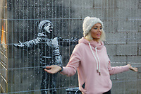 Pictured: People arrive to see and take pictures of the Banksy graffiti on a garage in Port Talbot, Wales, UK. Thursday 20 December 2018<br /> Re: The artist Banksy has confirmed that a new graffiti piece that has appeared in Port Talbot, south Wales is his.<br /> He announced on Instagram: &quot;Season's greetings&quot; - with a video of the artwork in the Taibach area of Port Talbot.<br /> The image appears on two sides of a garage in a lane near Caradog Street, depicting a child enjoying snow falling - the other side reveals it is a fire emitting ash.<br /> The owner of the garage said he had not slept over fears it might be vandalised.
