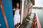 Beatriz dos Santos Rodrigues, 18, holds the dress she wore to her school prom as she stands in the doorway of her family's floating house, tied to a riverbank in Manaus, Brazil. Caritas, the social ministry of the Catholic Church, bought her the dress, which she will hand down to her little sister. The two girls participate in a Caritas program aimed at preventing sexual abuse and exploitation of children and adolescents.