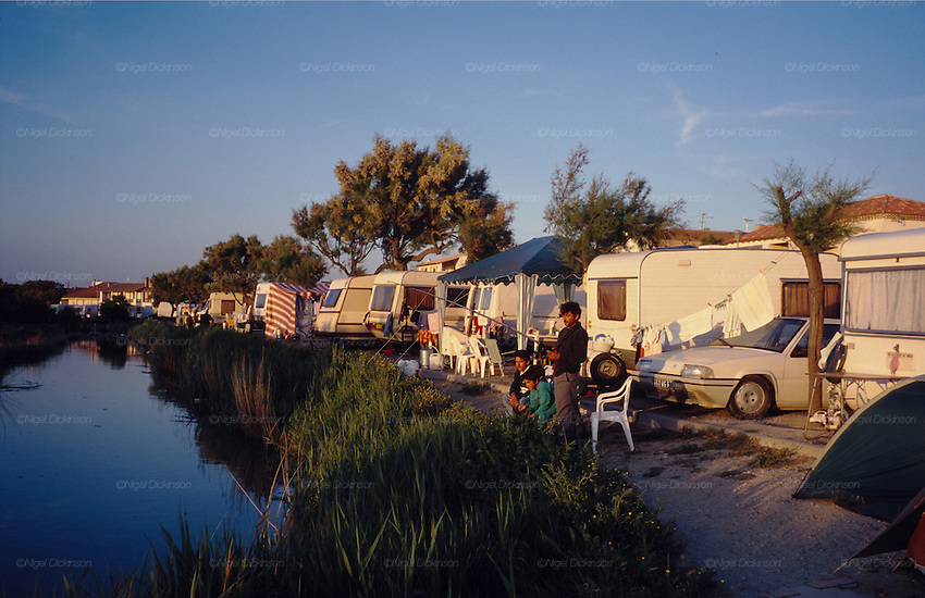 Europe, France, Camargue, Saintes Maries de la Mer, Gypsy Pilgrimmage 'Pelerinage des Gitans aux Saintes Maries de la Mer'. Fishing in the pond at sunset. Gypsies from all over the world come to celebrate their patron Saint Sara who is carried by them from the church to the sea-shore. May 24th and 25th every year.